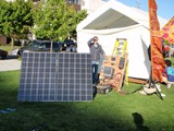 Solar-powerd-stage-built-for-Sustainable-Ballard,-Peter-checking-solar-azmuth-